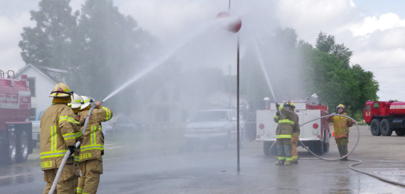 Firefighters spraying barrel